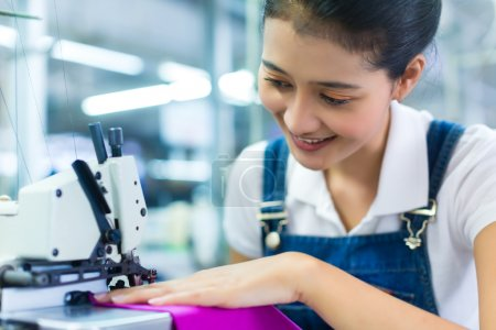 Photo for Asian Seamstress or worker in a Indonesian factory sewing with a industrial sewing machine, she is very accurate - Royalty Free Image
