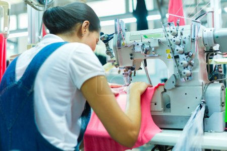 Photo for Asian Seamstress or worker in an Asian textile factory sewing with a industrial sewing machine, she is very accurate - Royalty Free Image