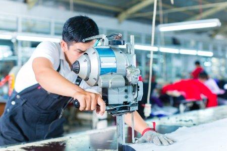 Photo pour Ouvrier indonésien utilisant un coupeur - une grande machine pour couper des tissus - dans une usine textile asiatique, il porte un gant de chaîne - image libre de droit