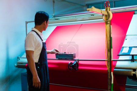 Asian worker controls fabrics