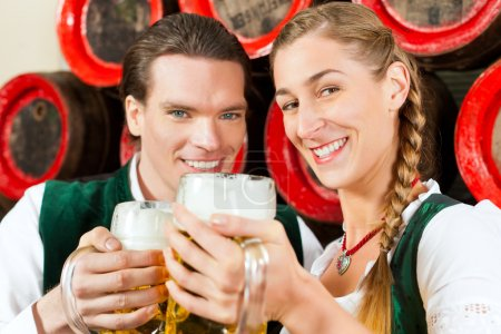 Couple drinking beer in brewery