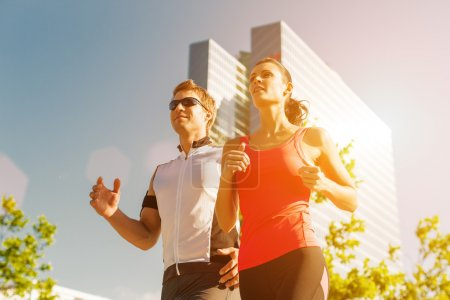 Photo for Urban sports - couple running or jogging for fitness in the city on beautiful summer day - Royalty Free Image
