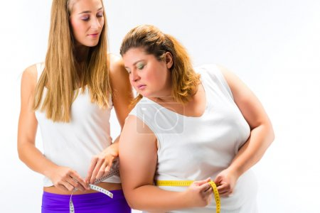 Women measuring waist with tape