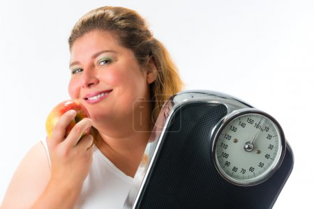 Obese woman with scale  and apple