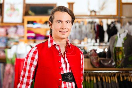 Man is trying Tracht or Lederhosen in a shop