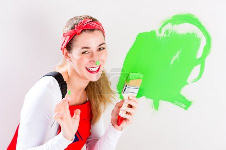 Woman having fun painting wall