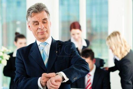 Photo pour Affaires - équipe dans un bureau, le cadre supérieur vérifie sa montre - image libre de droit