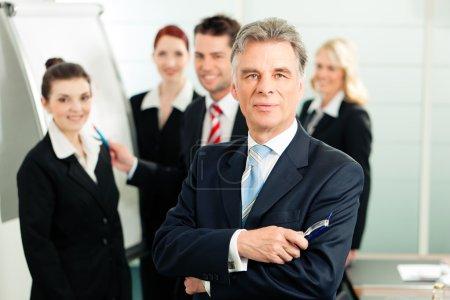 Photo pour Business - équipe dans un bureau, le cadre supérieur se tient devant - image libre de droit
