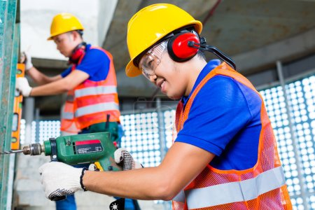 Photo pour Travailleurs indonésiens asiatiques de chantier de construction forant avec une machine ou une perceuse, niveau de bulle, protection d'oreille, gants et casque de hardhat dans un mur d'un bâtiment de tour - image libre de droit