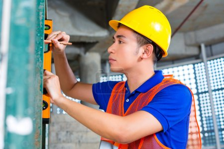 Photo for Asian Indonesian builder on construction site or craftsman with hardhat, bubble level and pen is controlling or checking a wall of a tower building - Royalty Free Image