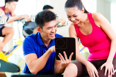 personal trainer with woman in fitness gym