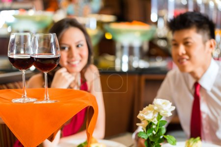 Photo for Waiter or steward serving man and woman or couple red wine in glasses on a tray in a fancy restaurant or hotel - Royalty Free Image