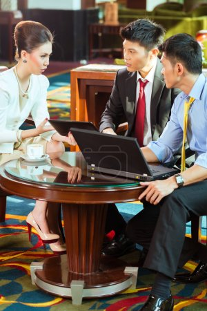 business people at meeting in hotel lobby