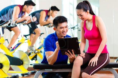 Photo pour Femme chinoise asiatique et entraîneur de fitness personnel en salle de gym discutant du programme d'entraînement et des objectifs pour l'entraînement - image libre de droit