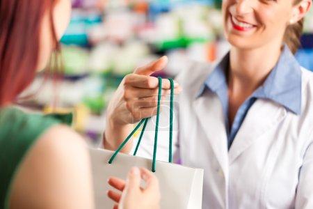 Female pharmacist in her pharmacy with a customer