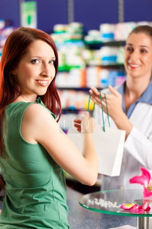 Female pharmacist in her pharmacy with a customer