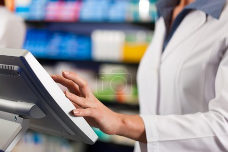 Female pharmacist at the cashier in pharmacy