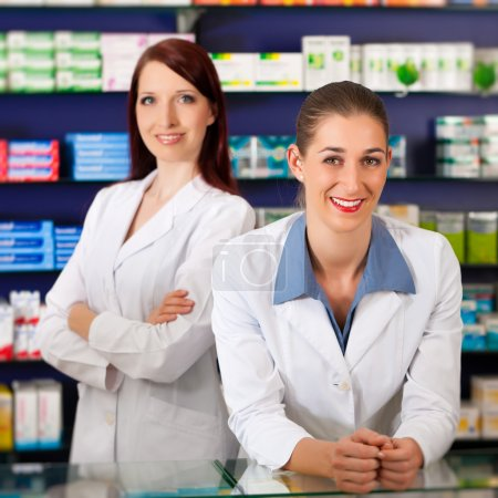 Pharmacist with assistant in pharmacy