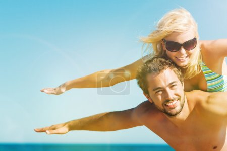 Man carrying his wife on beach in vacation
