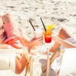 Two girls or woman drinking cocktails in beach clu...