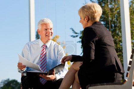 Photo pour Business Coaching en plein air - homme et femme dans la discussion de coaching - image libre de droit