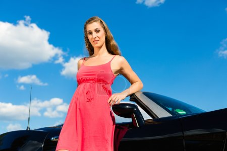 Young woman with cabriolet in summer on day trip