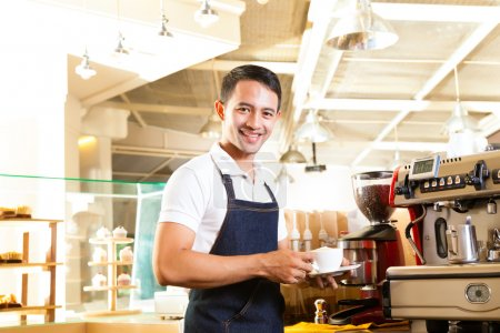 Photo for Coffeeshop - asian barista presents coffee in his shop - Royalty Free Image
