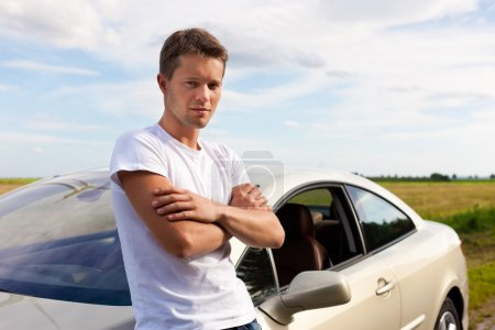 Photo for Man leaning on his car; presumably he has a break from driving - Royalty Free Image