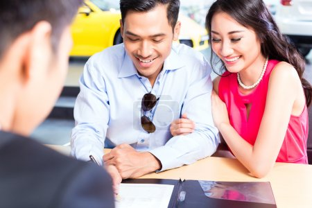 Couple signing sales contract for car at dealership