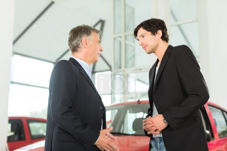 dealer and man with auto in car dealership