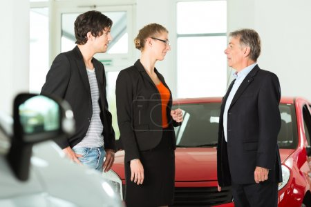 man with couple and autos in car dealership
