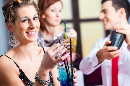 Photo for Woman drinking cocktails in fancy night club - Royalty Free Image