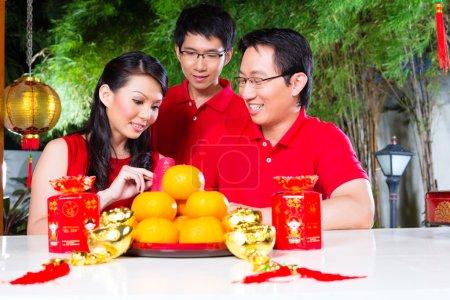 Photo pour Famille d'amis célébrer le Nouvel An chinois traditionnel avec un cadeau, portant des chemises rouges - image libre de droit