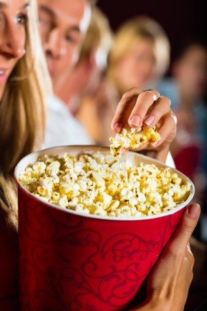 Girl eating popcorn in cinema