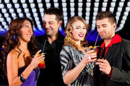 Photo pour Groupe de fêtards avec des cocktails dans un bar ou un club s'amuser - image libre de droit