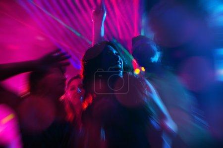 Photo pour Groupe de fêtards - hommes et femmes - qui dansent dans une discothèque à la musique - image libre de droit
