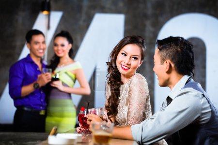 couples flirting and drinking at nightclub bar