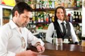 Barista s klientem v jeho kavárně nebo coffeeshop