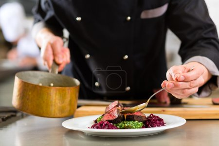 Photo for Chef in hotel or restaurant kitchen cooking, only hands, he is working on the sauce for the food as saucier, a Risotto - Royalty Free Image