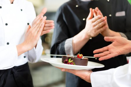 Photo for Chef team in restaurant kitchen with dessert, the colleagues applauding because the dish works great - Royalty Free Image