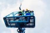 Stavební dělníci v hydraulické zvedací rampu na místě