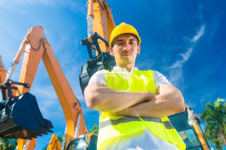 Asian builder in front of shovel excavator