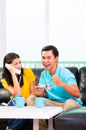 couple playing video games and phone