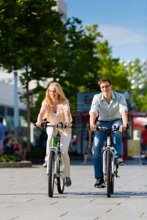 Urban couple riding bike in city