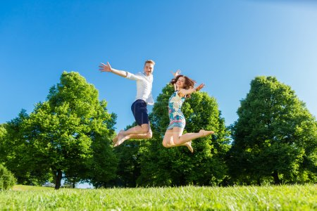Couple in love jumping on park lawn