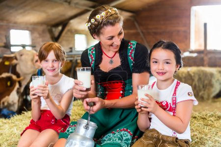 Photo for Bavarian mother sitting with children in cowhouse on hay bale drinking fresh milk - Royalty Free Image