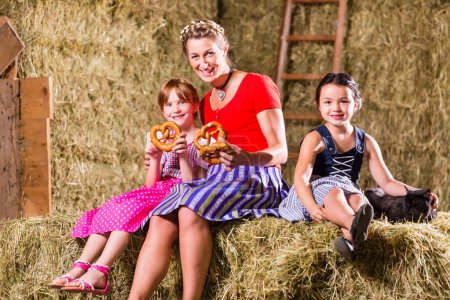 Photo for Bavarian mother and children sitting on hayloft with pretzels - Royalty Free Image
