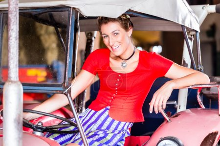 Photo for Bavarian woman with Dirndl dress driving tractor - Royalty Free Image