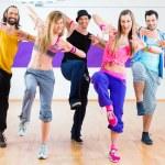 Group of men and women dancing zumba fitness chore...