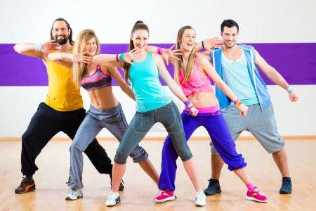 Photo pour Groupe d'hommes et de femmes dansant la chorégraphie de fitness zumba à l'école de danse - image libre de droit